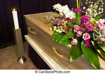 Coffin in morgue - A coffin with flower arrangement in a...
