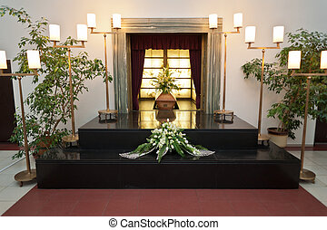 Wooden coffin with funeral flowers in crematorium