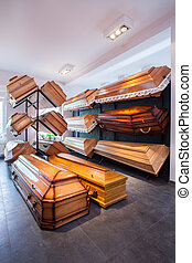 Coffins in funeral home - Wooden brown different coffins in...