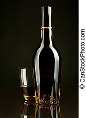 Cognac - A bottle and a glass of cognac in a black...