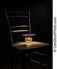 Cognac and cigar on wooden chair close up
