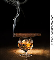 Cognac and cigar on wooden background close up