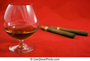 Cognac and cigars lying on red background