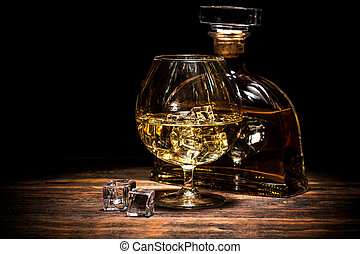 Cognac bottle and glass on the dark background.
