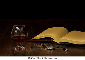 Cognac, cigar and an old book nearby