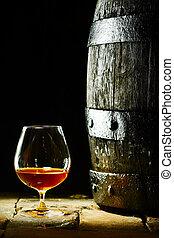 Cognac snifter and an old oak barrel