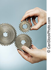 Cogs - Man designing a mechanical system using old cog gear...