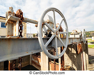 Cog wheel and chain of old dam closing mechanism of vintage sewage channel. Concrete weir with dirty water