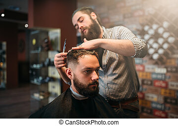 Coiffeur cutting by scissors hair of customer man