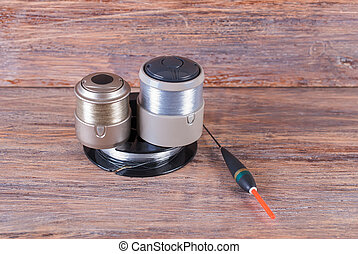 Coil with fishing line and float on wooden background