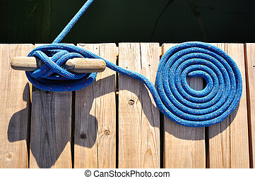 Coiled Blue Rope and Cleat on Marina Dock