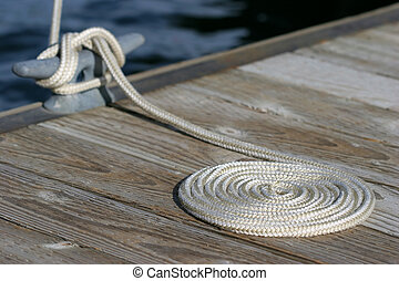 a neatly coiled rope leading to the cleat and a moored sailboat in yellowstone national park, wyoming