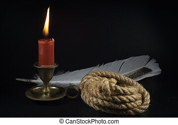 Coiled rope with burning candle and quill pen