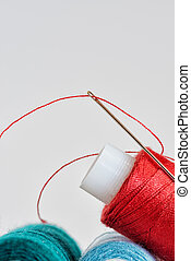 Coils of color threads and steel needle with a red thread