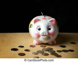 Coin bank like piggy and coins in front of it...