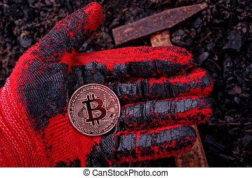coin bitcoin lies on a gloved hand against the ground and a hammer