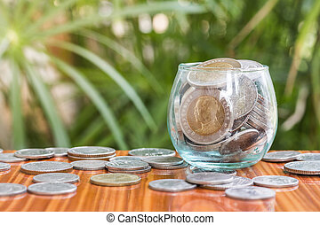 Coin in glass bottle with money stack step up growing growth saving money, Concept financial business investment. The background is natural green.
