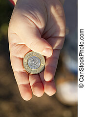 coin in the hands of a child