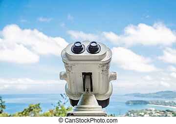 Coin Operated Binocular viewer next to the waterside promenade in Phuket looking out to the Bay. Landscape with beautiful cloudy sky and sea