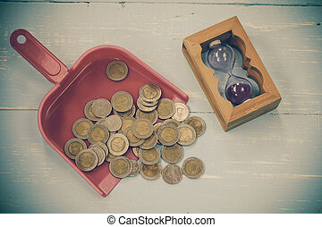 coin or money in dust pan on wood