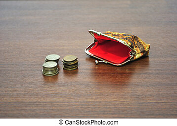 Coins and a small empty purse - Rouleau on a table and an ...