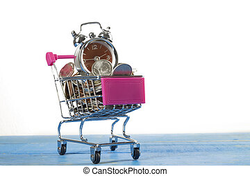 Coins and shopping trolley with clock