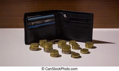 Coins appear in stop motion in front of the wallet