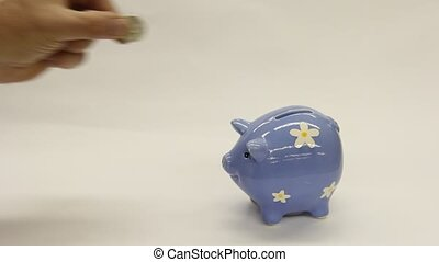 piggy bank - coins being put into a piggy bank