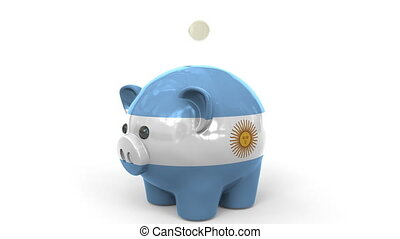 Coins fall into piggy bank painted with flag of Argentina....