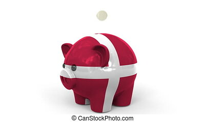 Coins fall into piggy bank painted with flag of Denmark....