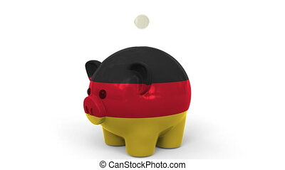 Coins fall into piggy bank painted with flag of Gemany....