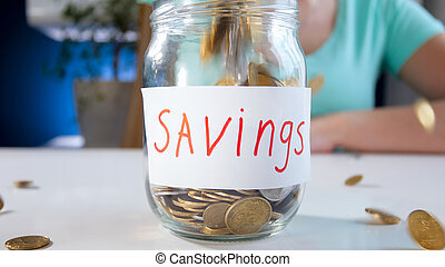 Coins falling in glass jar for money savings. Concept of financial investment, economy growth and bank savings
