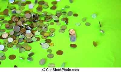 Coins falling on a green background, slow motion