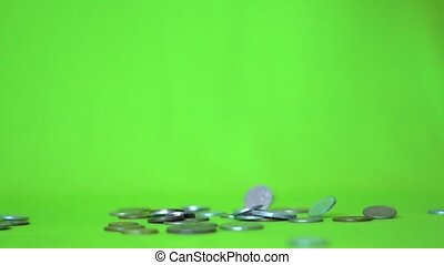 Coins falling on a green background, slow motion.