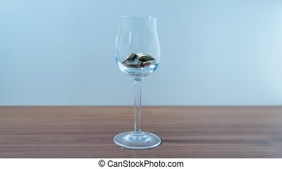 Coins fill glass goblet in stop motion