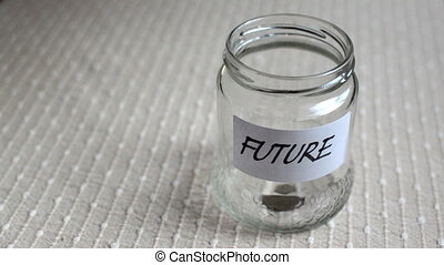 Coins filling in jar labeled for future - Coins filling and...