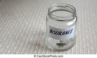 Coins filling in jar labeled for insurance - Coins filling...