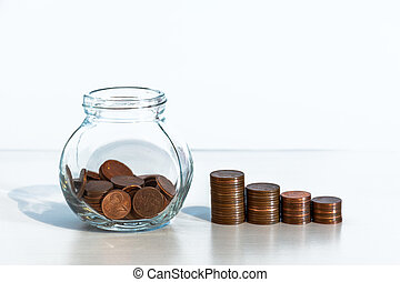 Coins in a glass jar and stacks of coins