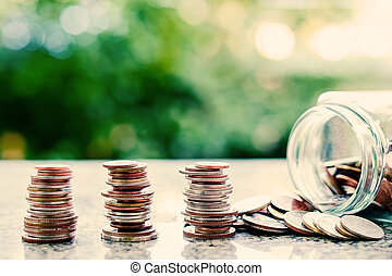 Coins in glass jar and outside, Thai currency money on blurred natural green background