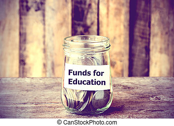 Coins in glass money jar with Funds for Education label