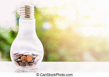 Coins in light bulb bottle shape against blurred natural green background