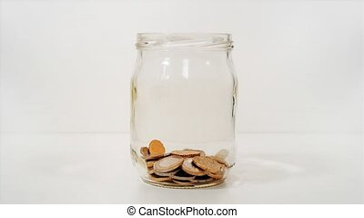Coins in the glass jar in stop motion
