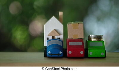 Coins, model house and box place on wood car on nature background. Property investment and house mortgage financial. panning shot and slow motion shot