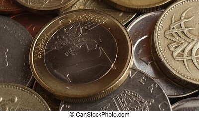 coins of different countries with one euro coin on top spins, macro shot.