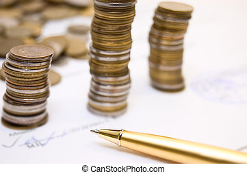 Coins on written contract with pen
