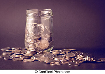 Coins spilling out of a glass bottle with filter effect retro vintage style