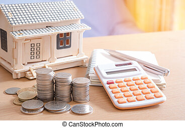 Coins stacked savings, calculator, notebook with pen ,concept for saving or investment for a house