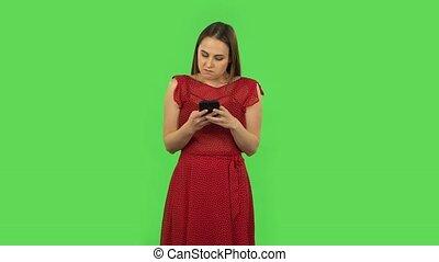colère, tendre, robe verte, elle, téléphone., écran, girl, texting, rouges