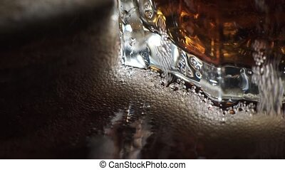 Cola and ice in glass. Close up of Cola with Ice cubes and...