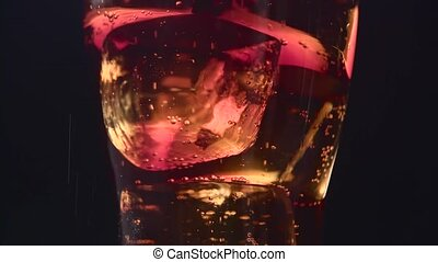 Cola fills a transparent glass filled with ice cubes. Black...